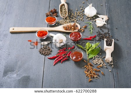 fresh and dried chili fruits, peppercorn, pepper powder, sauce and garlic, bay leaves on old black wooden table background #622700288