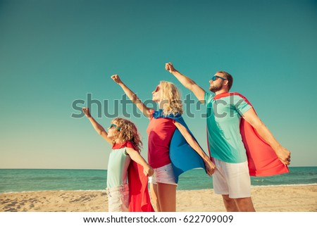 Ready to travel! Family of superheroes on the beach. Child, mother and father having fun outdoor. People against sea and sky background. Summer vacation concept