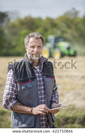 farmer examine quality of soil in field and using a digital tablet #622710866