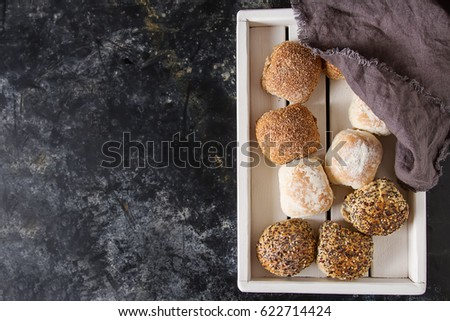 Fresh homemade bread from wheat. Dark background. A wooden tray. Top view. Copy space. Selective focus. The concept of a healthy diet or dietary nutrition #622714424