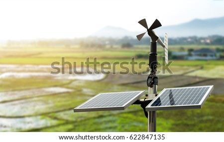 Smart agriculture and smart farm technology concept. Revolving vane anemometer, a meteorological instrument used to measure the wind speed and solar cell system with rice field background. #622847135