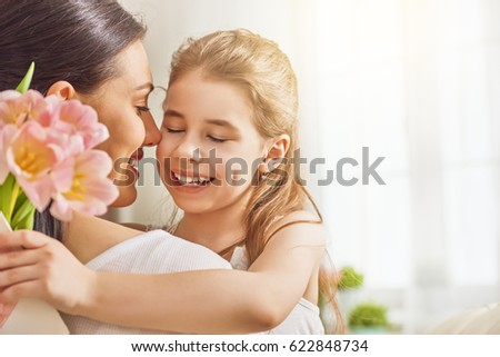 Happy mother's day! Child daughter congratulates mom and gives her flowers tulips. Mum and girl smiling and hugging. Family holiday and togetherness. #622848734