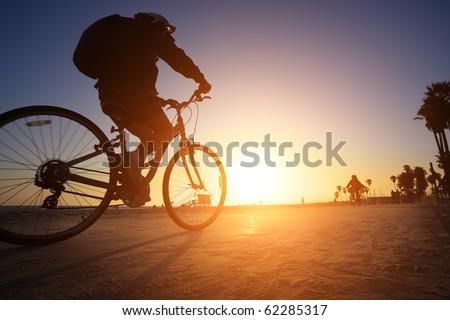 Biker silhouette riding along beach at sunset #62285317
