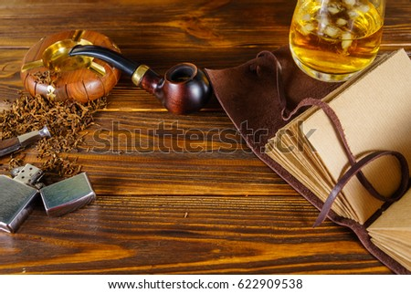 Smoking pipe and notebook on the table #622909538
