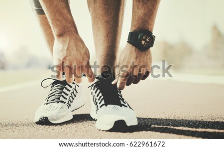 Tying sports shoe. A young sportsman getting ready for athletic and fitness training outdoors. Sport, exercise, fitness, workout. Healthy lifestyle #622961672