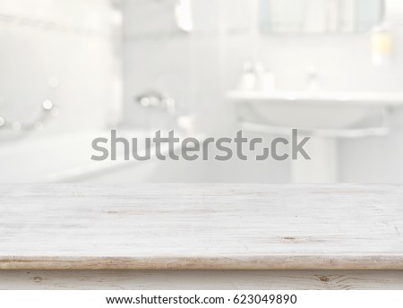 Wooden table in front of blurred bathroom interior as background. Royalty-Free Stock Photo #623049890
