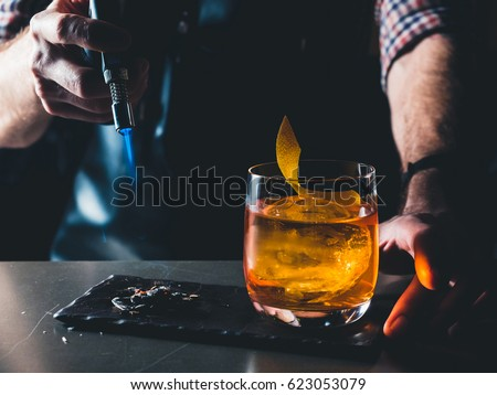 Bright orange Old Fashioned Cocktail with whiskey on a black board. Decorated with burning coal with the smoke. Bartender hand burning the cocktail decoration. Perfect Serve example. Horizontal Royalty-Free Stock Photo #623053079