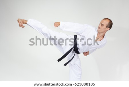 Adult athlete trains a kick on a gray background #623088185