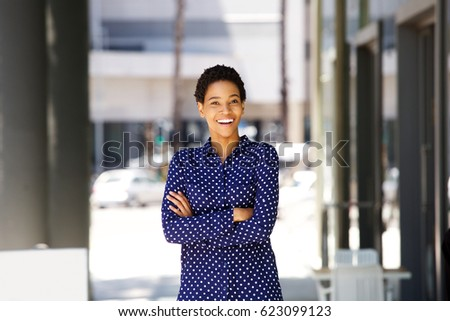 Portrait of confident business woman smiling outside in the city #623099123