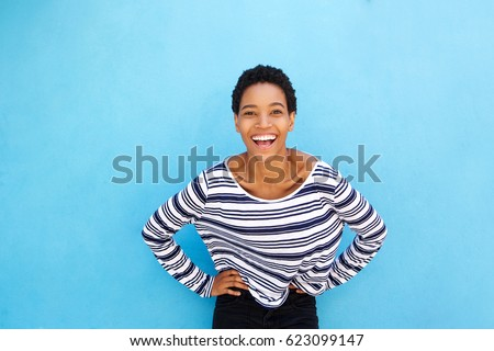 Portrait of attractive young african american young woman smiling against blue wall #623099147
