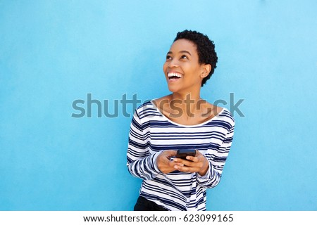 Portrait of attractive young african american woman holding cellphone by blue wall #623099165