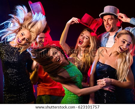 Dance party with group people dancing . Women and men have fun in night club. Happy girl with tousled hair on foreground . Back light on girls hair. #623101757