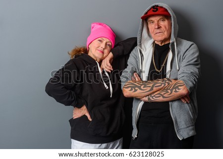 Old couple dressed in hip-hop style. Stylish grandma leant on her husband. Horizontal photo with gray background.