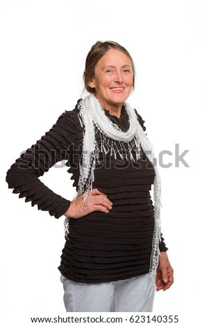 Vertical pic of a beautiful grandmother. Old woman dressed in casual style: light bottom and dark top. Her gray scarf decorated with knotted fringe. Stylish woman in a lifted mood.