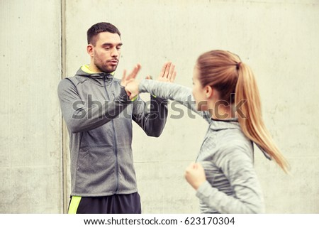 fitness, sport, people, exercising and martial arts concept - young woman with trainer working out self defense strike on city street Royalty-Free Stock Photo #623170304