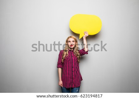 Beautiful young woman holding blank speech bubble over grey background