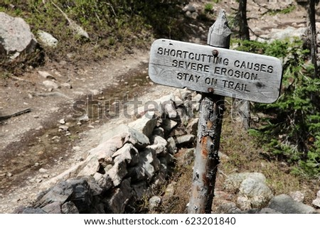 National park sign: trail shortcutting causes severe erosion. Stay on trail! Rocky Mountains National Park, Colorado. Royalty-Free Stock Photo #623201840