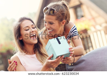A picture of two girl friends making a surprise birthday present