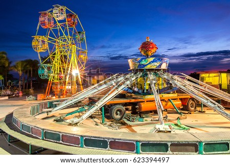 ferris wheel and gravity maching in movable amusement park at sunset time in Thailand #623394497