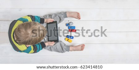 Boy using ipad / laptop while playing with toy cars on a carpet at home. Tablet pc hero header image. Boy using digital tablet while lying on wooden floor.