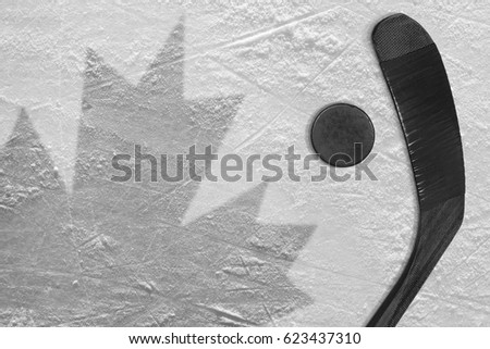 Hockey puck, stick, and the image of the Canadian flag on the ice. Concept
