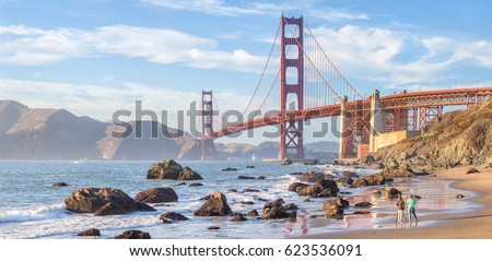 Classic panoramic view of famous Golden Gate Bridge seen from scenic Baker Beach in beautiful golden evening light on a sunny day with blue sky and clouds in summer, San Francisco, California, USA #623536091