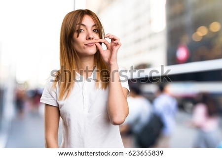 Beautiful young girl making silence gesture on unfocused background #623655839