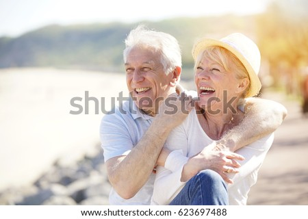 Senior couple relaxing by the sea on sunny day #623697488