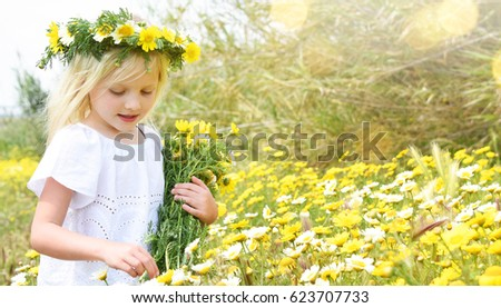 Children blond girl with daisy flowers. Summer vacation time. Country side. #623707733