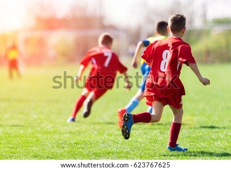 Kids soccer football - young children players match on soccer field  Royalty-Free Stock Photo #623767625