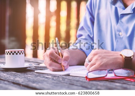 Businessmen Hands writting on wood table at coffee shop. #623800658