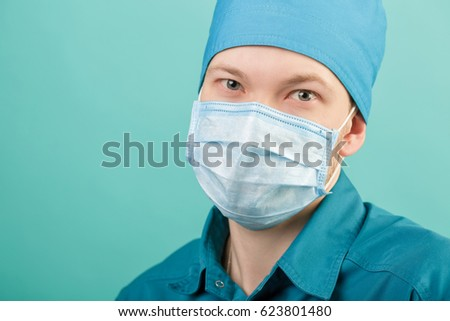 male surgeon in mask looking at camera on blue background, close up #623801480