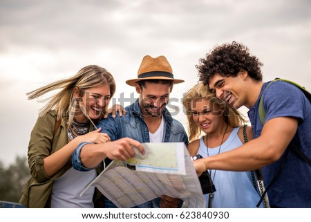 Group of tourists searching for places on their map outdoors. Royalty-Free Stock Photo #623840930