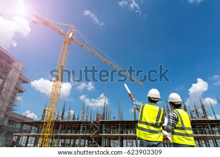 Civil engineer checking work with walkie-talkie for communication to management team in the construction site #623903309