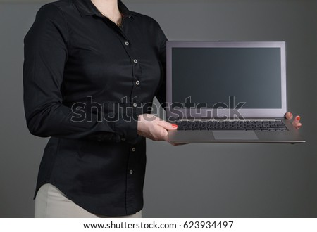 Business woman presenting a software or showing an application. Girl holding laptop with dynamic pose and black collared shirt. Empty screen with copy space for text or content. Gray background. #623934497