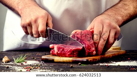 Man cutting beef meat. Royalty-Free Stock Photo #624032513