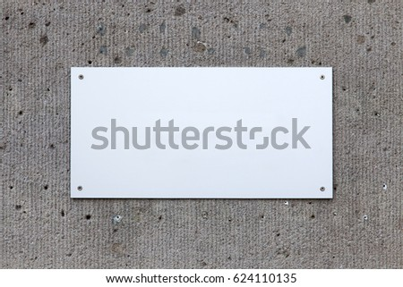 Silver metal sign ready for copy, on concrete wall.