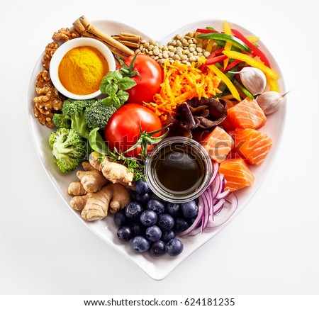 Heart-shaped plate of healthy heart foods with acai, lentils, soy sauce, ginger, salmon, carrot, tomato, turmeric, cinnamon, walnuts, garlic, peppers, broccoli, basil, onion isolated on white