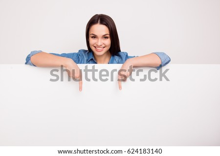 Cheerful cute girl is standing behind the white blank banner and pointing down at a copyspace Royalty-Free Stock Photo #624183140
