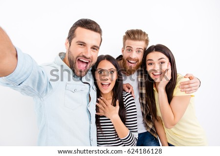 Group of excited friends making selfie on the camera of smartphone showing great emotions of amazement and excitement on white background in casual clothes