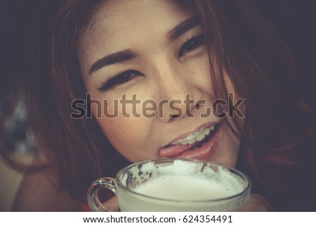 Closeup Asian girl holding milk cup coffee shop. dark vintage tone.Woman having healthy diet breakfast enjoy drinking hot milk glass tea time. selective focus lick her lips stare at you looking ahead. #624354491