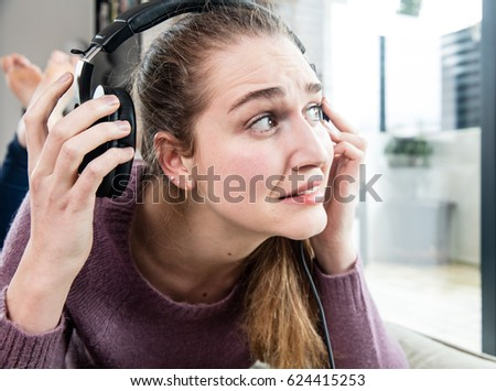 surprised candid beautiful young woman removing one headphone from her ear for noise or loud music, grinding teeth, suffering from tinnitus or headache, real people #624415253