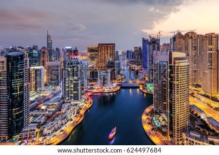 Spectacular view of a big modern city at night. Dubai Marina creek with illuminated skyscrapers. Scenic nighttime skyline. Popular travel destination.