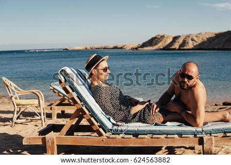 young couple sitting on a lounger on the on the beach #624563882