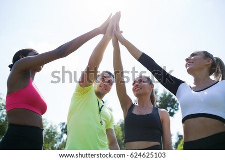 You are my champions. Group circle of  happy athletic young women in sportswear holding hands together with coach in green summer park  outdoors #624625103