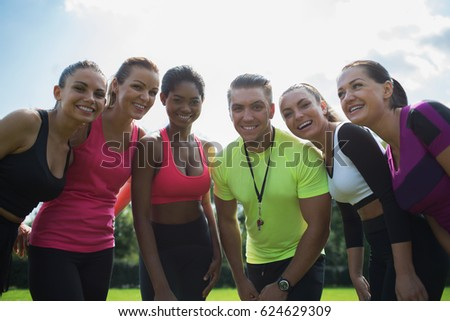 We are the best sport team ever! Group of  athletic young women in sportswear with coach standing together, looking at camera and smiling in green summer park  outdoors