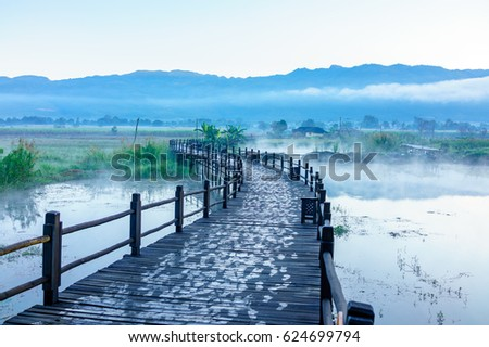 The curved wooden bridge over a misty lake with a blur background of trees and village, on a lake shore and low cloud in front of a mountain range, early in the morning #624699794