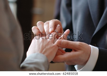 Groom putting a wedding ring on bride's finger #62485018
