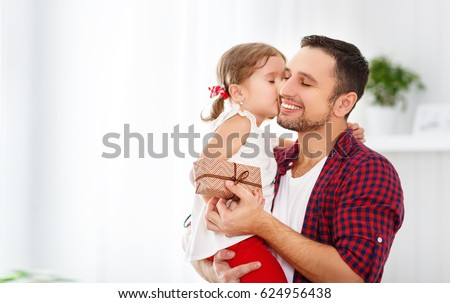 Father's day. Happy family daughter hugging dad and laughs on holiday