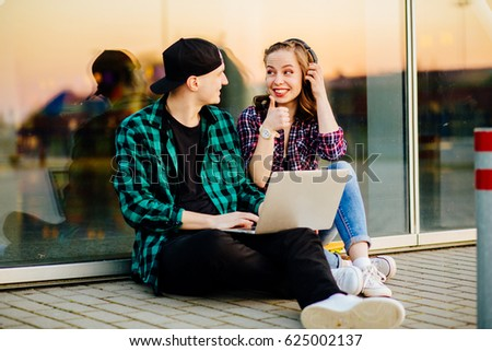 Happy weekend concept. Portrait of happy hipster couple in trendy casual clothing sitting near big window and using laptop and laughing. Sunny spring or autumn weather. Street style. Outdoor shot. #625002137